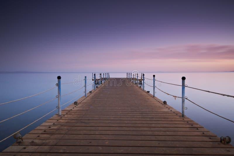 La jetée ou la jetée en bois sur la réflexion de coucher du soleil et de ciel de mer arrosent Longue exposition, Dahab, Egypte photo libre de droits