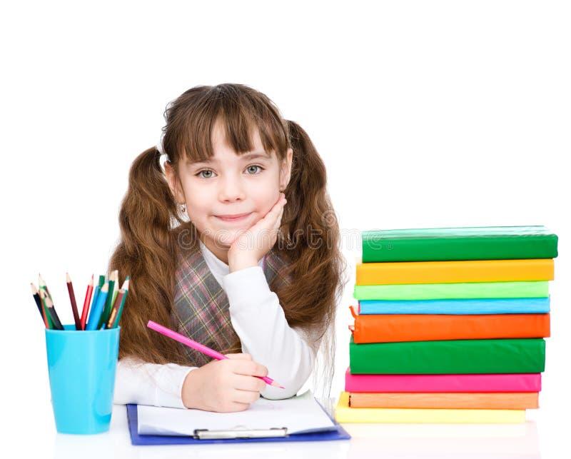 La jeune écolière écrivent l'examen D'isolement sur le fond blanc images libres de droits