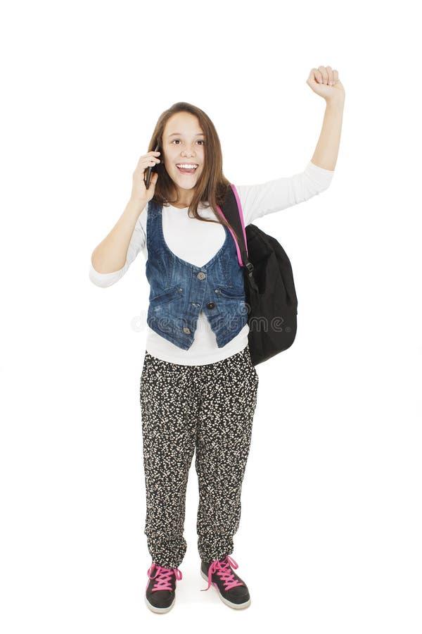 La jeune écolière heureuse appelle avec un téléphone portable image libre de droits