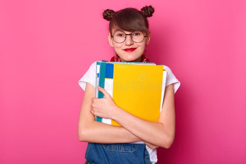 La jeune écolière heureuse embrasse les reliures colorées d'isolement sur le fond rose La fille de sourire semble heureuse, passe image libre de droits