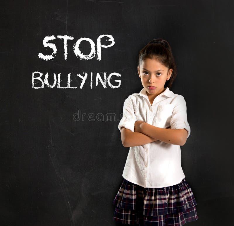 La jeune écolière mignonne latine effrayée et triste et les mots cessent d'intimider le texte écrit avec la craie photo libre de droits