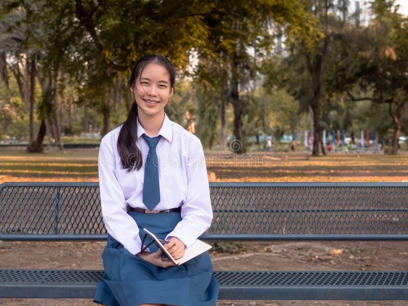 La jeune étudiante asiatique gaie dans le style de la Thaïlande d'uniforme scolaire tient les livres dans des ses mains et se rep photos stock