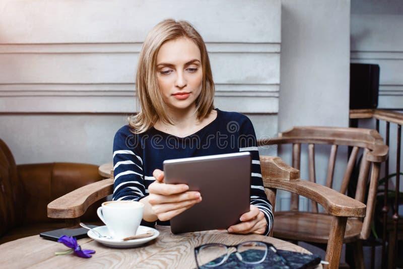 La jeune étudiante cause sur le comprimé numérique avec l'ami tout en se reposant en café, femme attirante à l'aide de l'ordinate photographie stock libre de droits