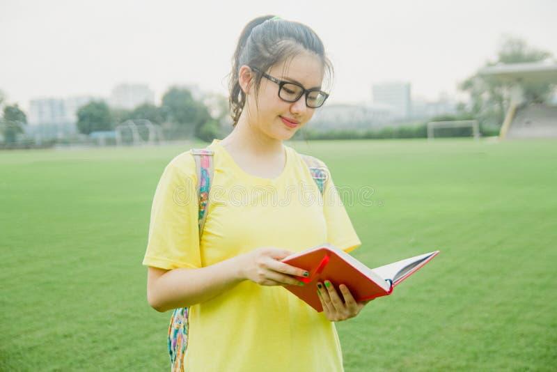 La jeune étudiante lit un livre sur le champ d'herbe pendant l'après-midi dans le campus photographie stock