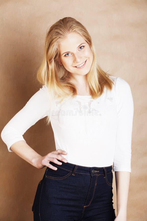 La jeune adolescente fraîche de blong a sali avec sa fin de sourire de cheveux sur le fond brun chaud, concept de personnes de mo photographie stock
