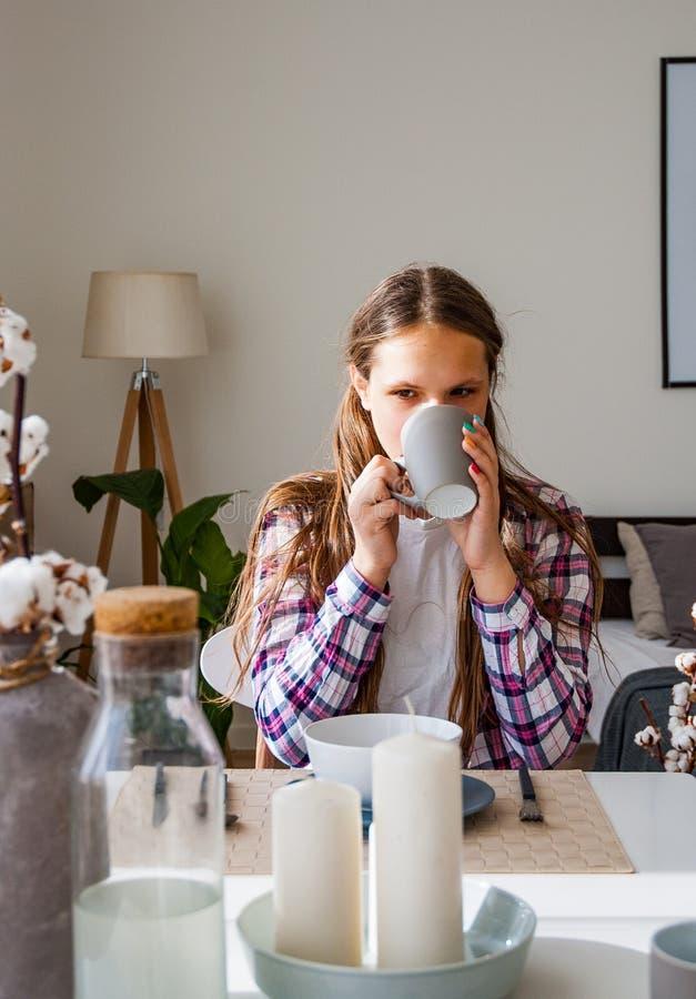 La jeune adolescente prend le petit déjeuner et le thé ou le café potable dans la cuisine photo stock