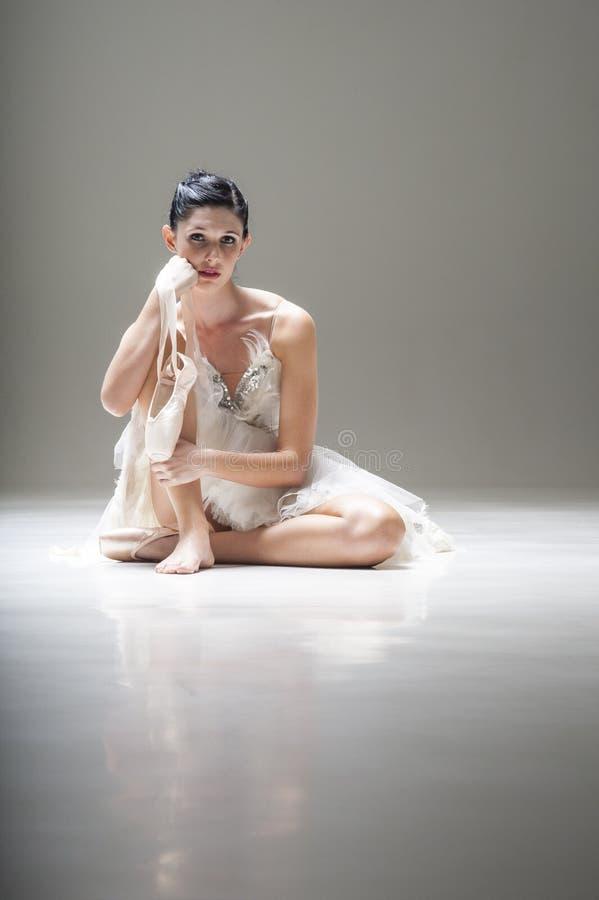 La jeune ballerine attirante s'asseyant sur le plancher fonctionnant avec elle a dirigé des chaussures de ballet image libre de droits
