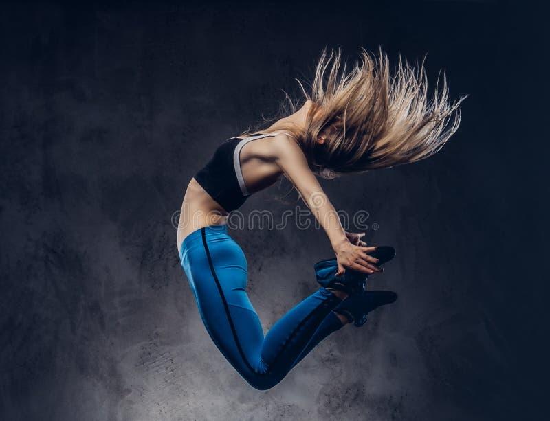 La jeune ballerine blonde dans les vêtements de sport danse et saute dans un studio D'isolement sur un fond foncé photographie stock