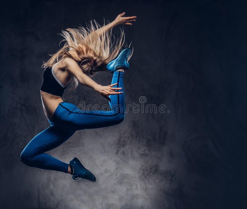 La jeune ballerine blonde dans les vêtements de sport danse et saute dans un studio Remboursement in fine photos stock