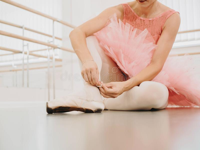 La jeune ballerine dans le costume rose de tutu enveloppe les rubans en soie blancs du pointe et des liens supérieurs mous de cha photographie stock libre de droits