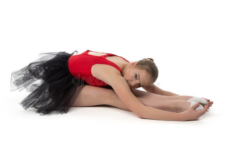 La jeune ballerine fait étirer des exercices photo stock