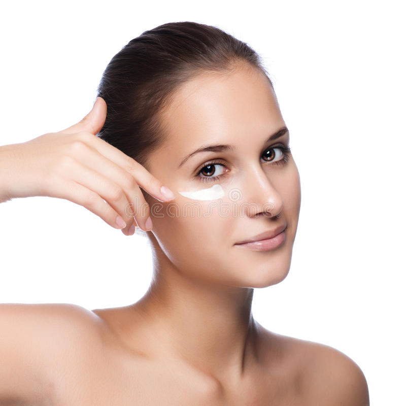 La jeune belle application de femme hydratent la crème image stock