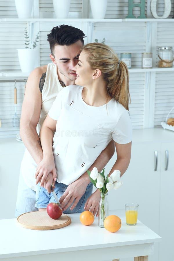 La jeune belle coupe affectueuse de couples porte des fruits pour faire l'amusement frais de jus et de avoir dans la cuisine à la photos stock