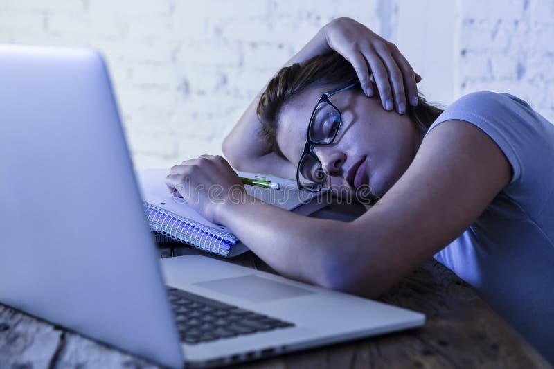 La jeune belle et fatiguée fille d'étudiant dormant prenant un petit somme se trouvant sur le bureau à la maison d'ordinateur por photos stock