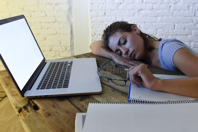 La jeune belle et fatiguée fille d'étudiant dormant prenant un petit somme se trouvant sur le bureau à la maison d'ordinateur por photo stock
