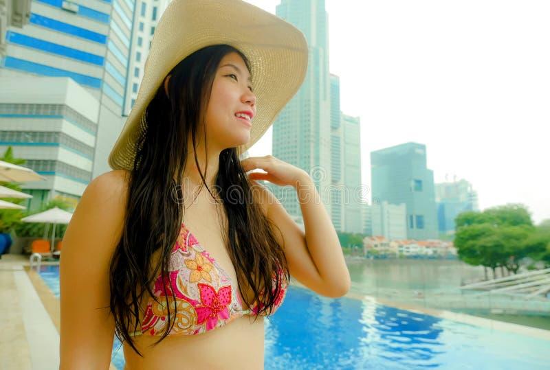 La jeune belle et heureuse femme de touristes chinoise asiatique dans le luxe de chapeau d'été à la piscine d'infini d'hôtel appr photographie stock libre de droits