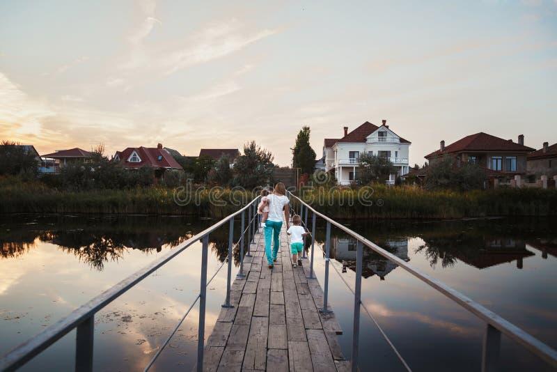 La jeune belle famille au pont, la mère et les enfants retournent à la maison de l'extérieur photographie stock libre de droits