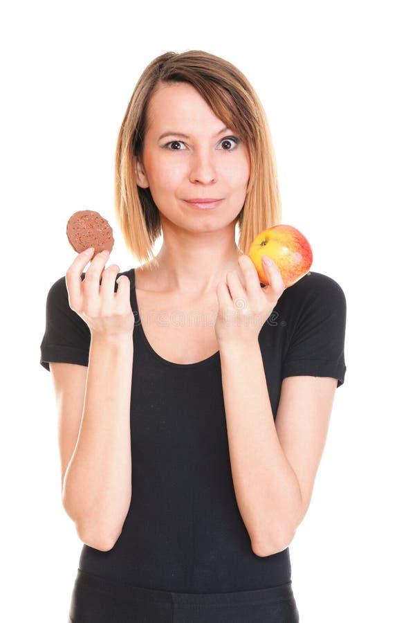 La jeune belle femelle choisissent du gâteau doux et de la pomme rouge images stock