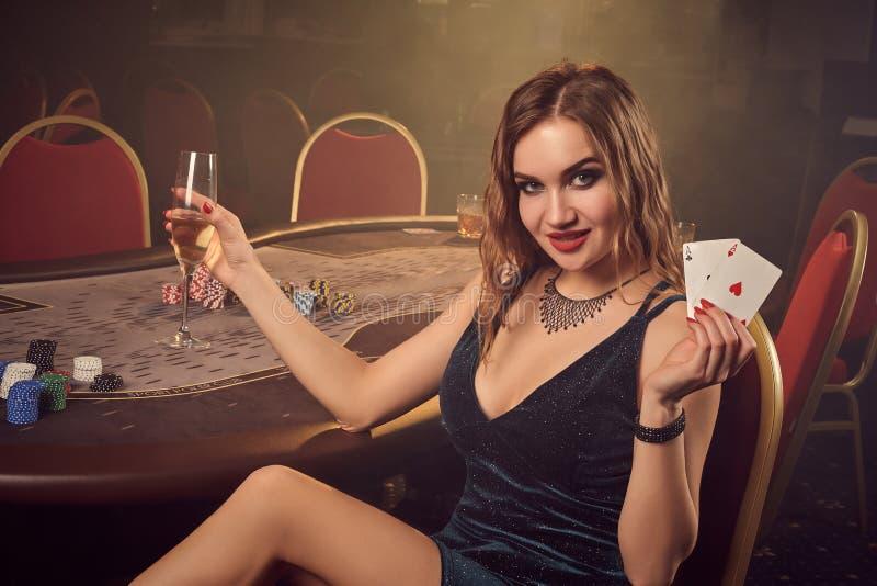 La jeune belle femelle pose la séance sur une chaise contre une table de tisonnier dans le casino de luxe photos libres de droits