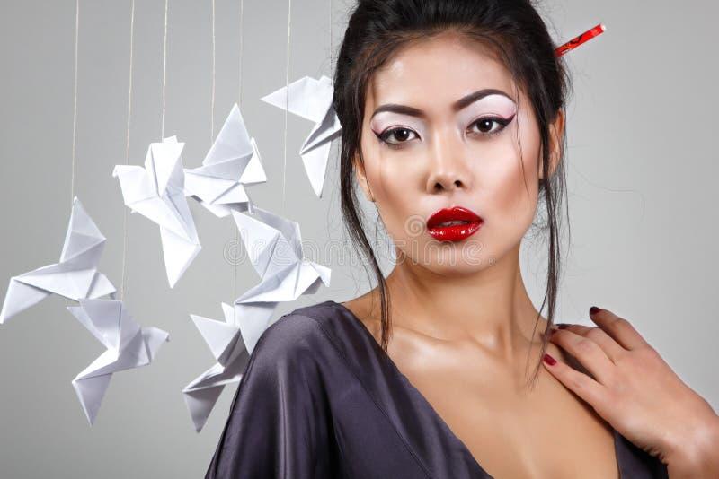 La jeune belle femme asiatique avec l'origami empaquettent des pigeons photo libre de droits
