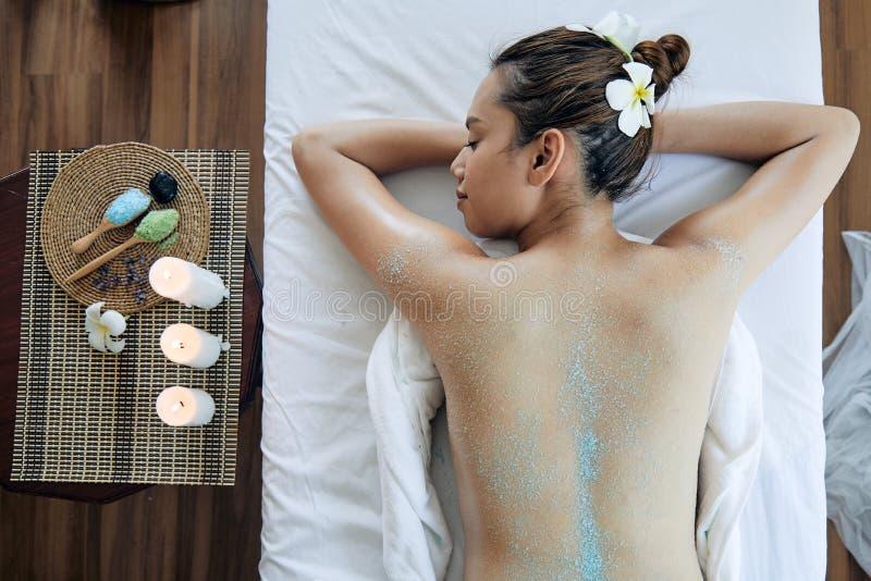 La jeune belle femme asiatique obtiennent le traitement de station thermale de sel sur le dos photos stock