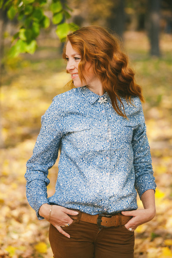 La jeune belle femme aux feuilles d'automne et l'érable jaune de chute par photographie stock libre de droits