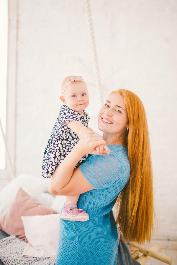 La jeune belle femme avec de longs cheveux rouges dans une robe bleue tient un enfant sur ses mains une blonde d'an près du lit s photographie stock