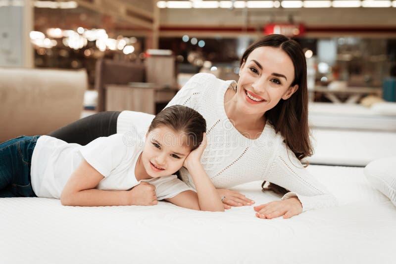 La jeune belle femme avec la petite fille mignonne se trouve sur le lit dans le magasin de matelas images libres de droits