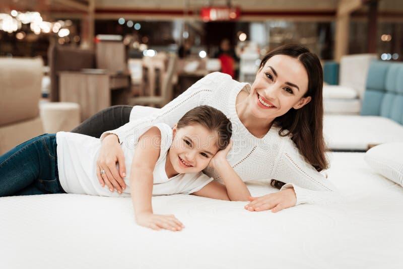La jeune belle femme avec la petite fille mignonne se trouve sur le lit dans le magasin de matelas images stock