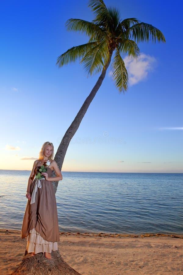La jeune belle femme avec une rose sur un palmier sur seacoast.portrait contre la mer tropicale photo stock