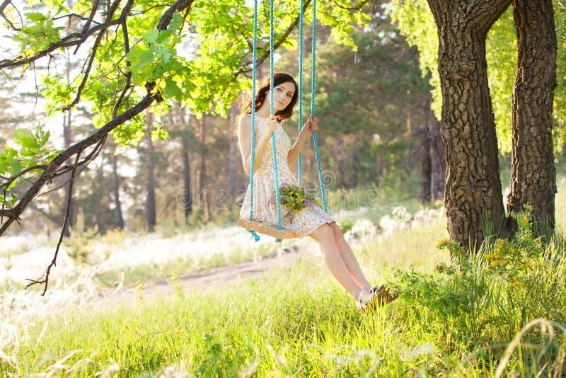 La jeune belle femme balance sur une oscillation dans la forêt d'été image stock