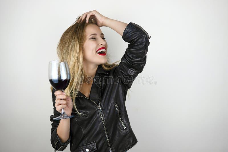 La jeune belle femme blonde sexy utilisant la veste en cuir noire boit du vin du verre riant sur le blanc d'isolement photo stock