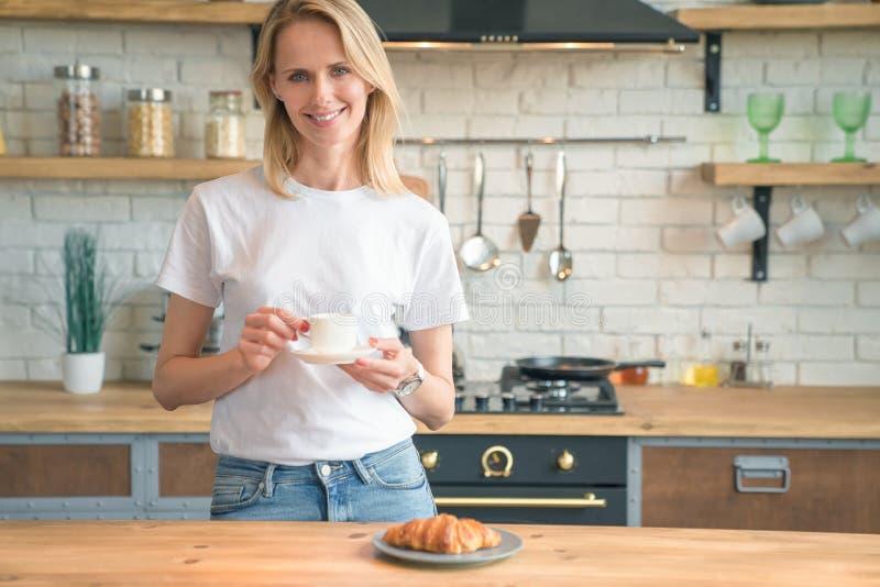 La jeune belle femme boit du café dans la cuisine pendant le matin et sourit regardant la caméra Chemise blanche de port et photos libres de droits