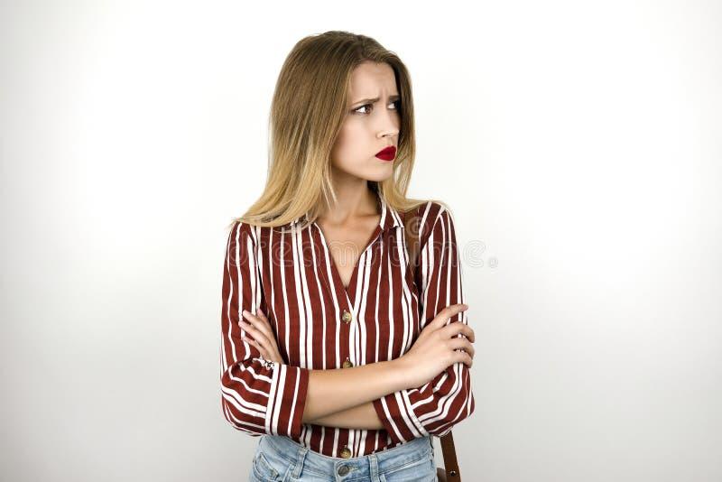 La jeune belle femme bouleversée blonde portant les caleçons à la mode de denim de chemise rayée et le mini sac en cuir ont isolé images stock