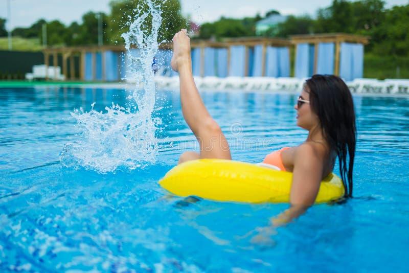La jeune belle femme détend dans la piscine avec l'anneau en caoutchouc photos libres de droits