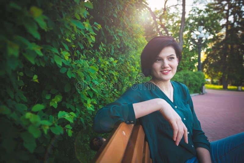 La jeune belle femme détend en parc photos stock
