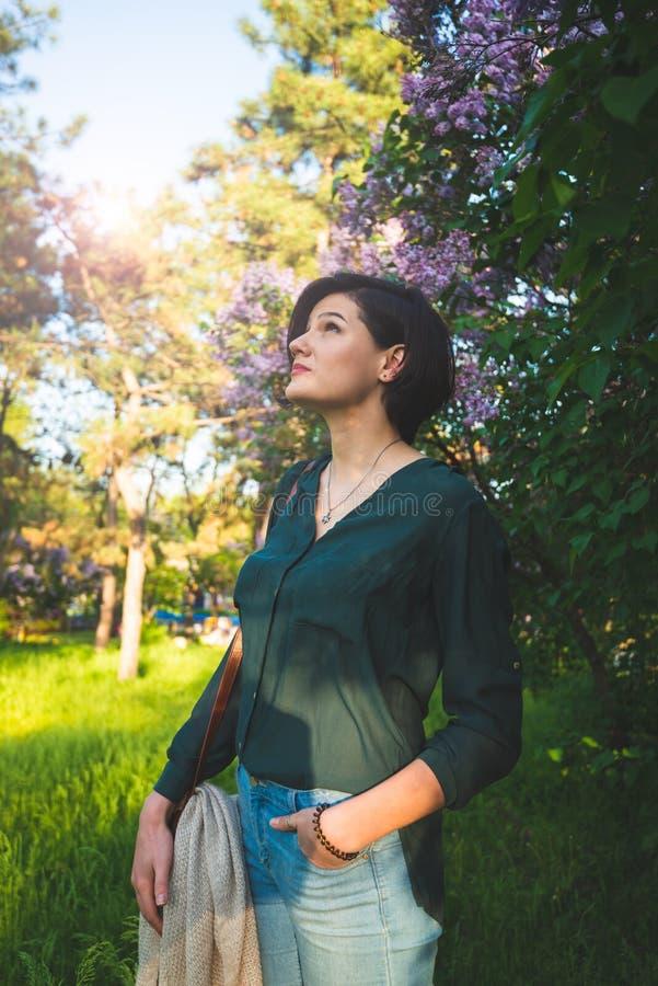 La jeune belle femme détend parmi les buissons fleurissants du lilas photographie stock