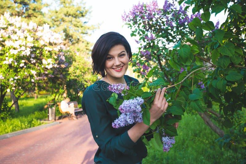 La jeune belle femme détend parmi les buissons fleurissants du lilas images libres de droits