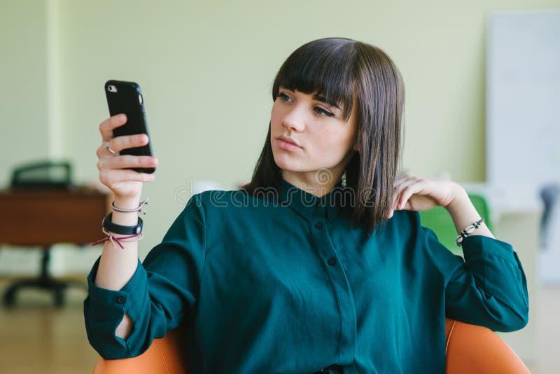 La jeune belle femme d'affaires s'asseyant dans un bureau moderne sur une chaise et utilisent le téléphone Travail de coupure images stock