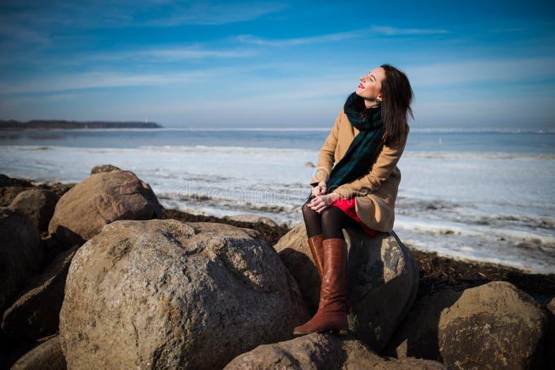La jeune belle femme dans des vêtements élégants avec l'écharpe s'assied sur le littoral dans la saison d'hiver images libres de droits