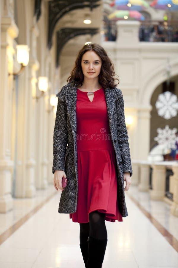 La jeune belle femme dans la robe rouge marche dans le magasin image stock