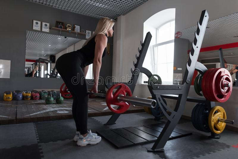 La jeune belle femme dans les vêtements de sport noirs fait des exercices de force avec un barbell dans un gymnase moderne Entraî images stock