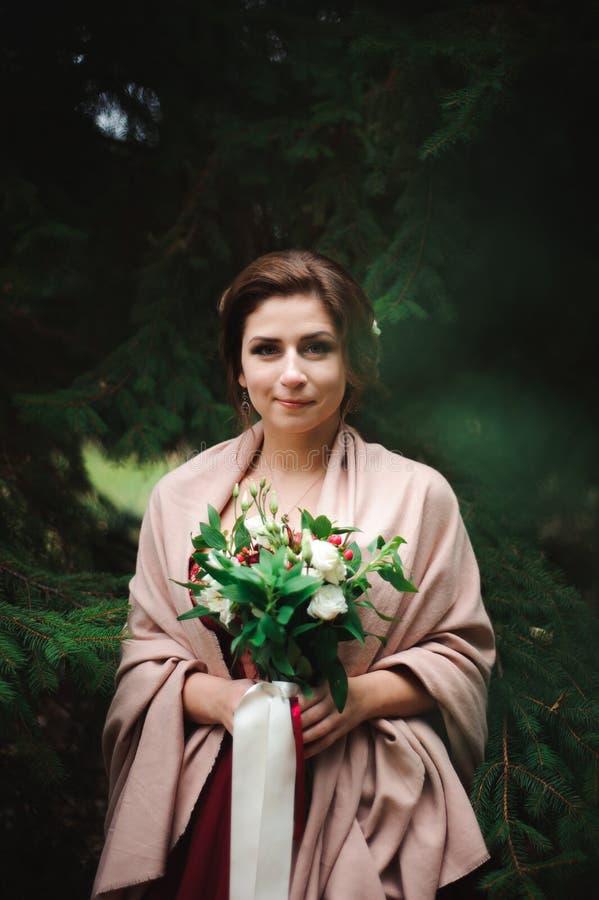 La jeune belle femme dans une robe l'épousant avec un bouquet images stock