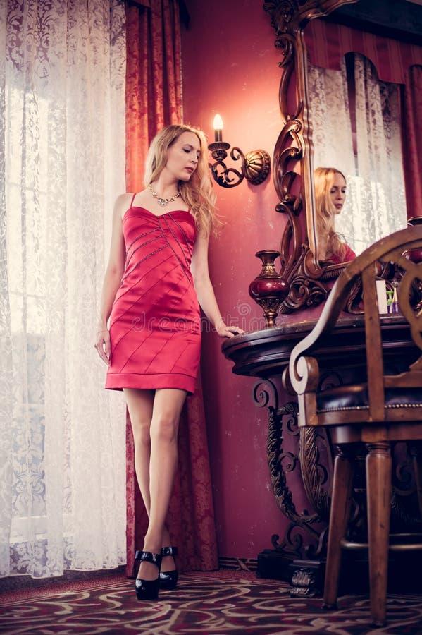 La jeune belle femme dans une robe rouge ?l?gante est dans une chambre avec un int?rieur cher de cru chic photographie stock libre de droits