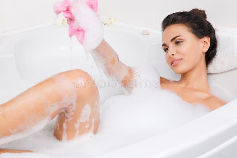 La belle jeune femme prend le bain moussant images stock