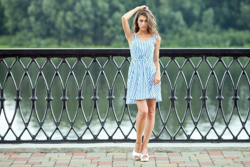 La jeune belle femme de portrait intégral dans le bleu blanc a barré la robe, parc de rver d'été dehors image libre de droits