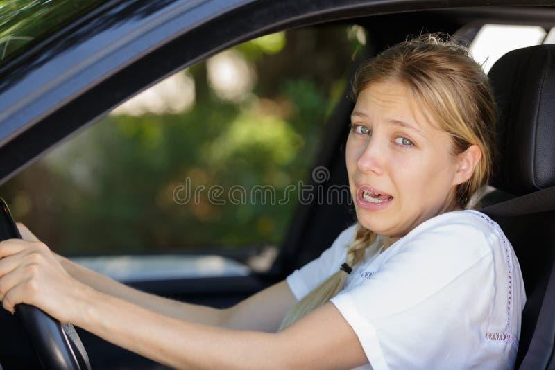 La jeune belle femme a effrayé et a soumis à une contrainte tout en conduisant la voiture images libres de droits