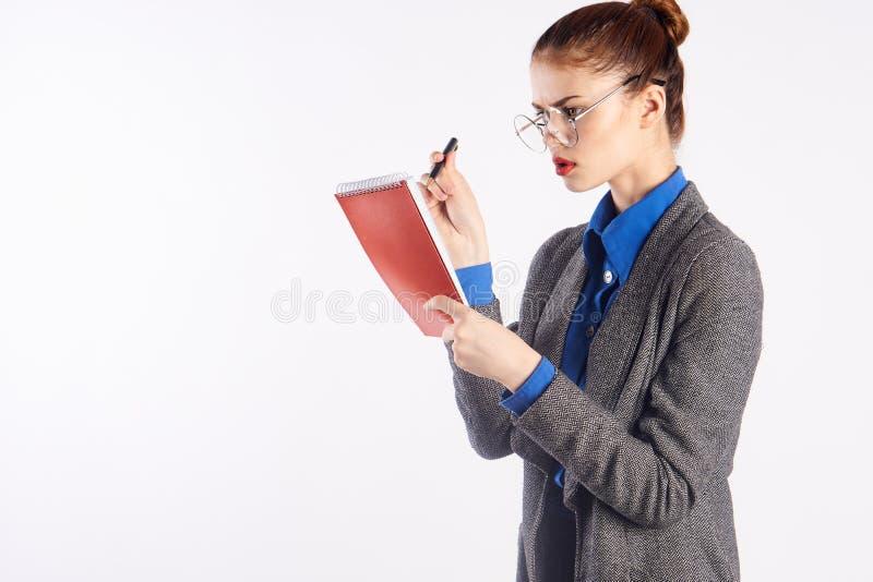 La jeune belle femme en verres vérifie le travail, émotions, professeur, fond d'isolement par blanc image stock