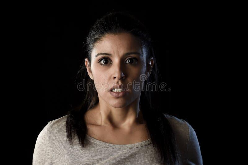 La jeune belle femme espagnole effrayée dans le choc et la surprise font face à l'expression d'isolement sur le noir image stock