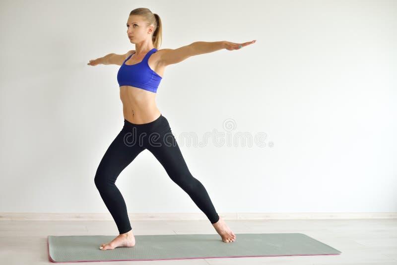 La jeune belle femme faisant le yoga pose d'intérieur sur le fond gris Fille pratiquant son corps dans le gymnase images libres de droits